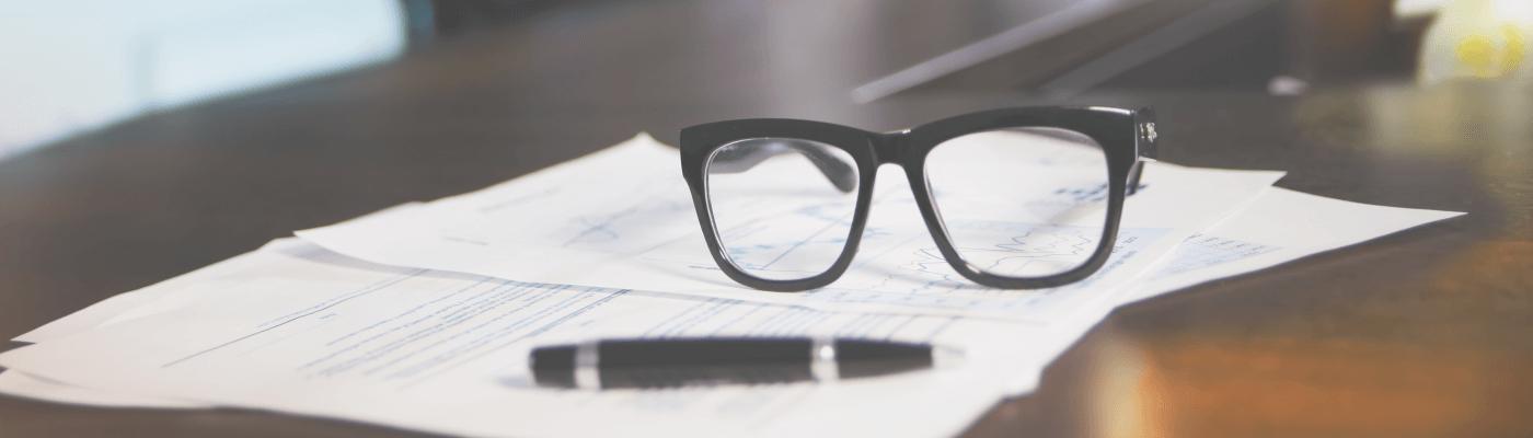 Umowa na stronę internetową, na której leżą długopis i okulary